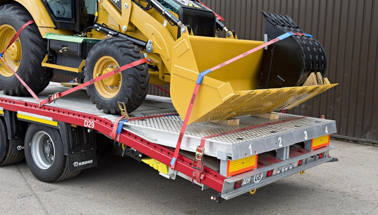 Backhoes loaded, the ramps form part of the flatbed trailer