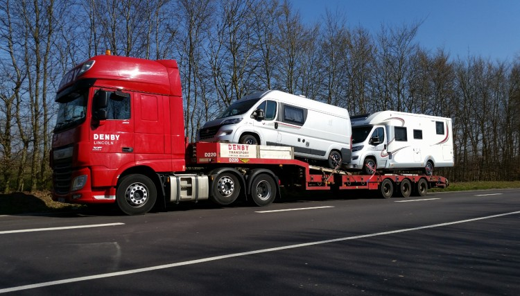 Motorhomes loaded onto a step frame flatbed trailer